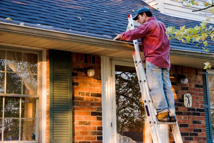 Man,Cleaning,Gutters,On,Ladder